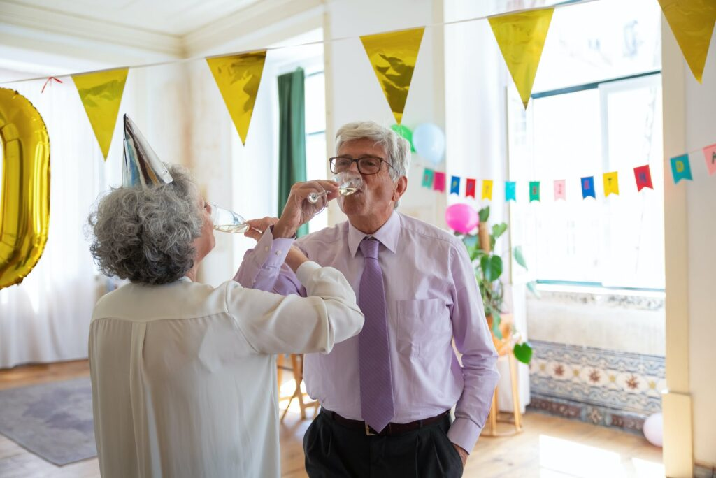 elderly couple drinking champagne together